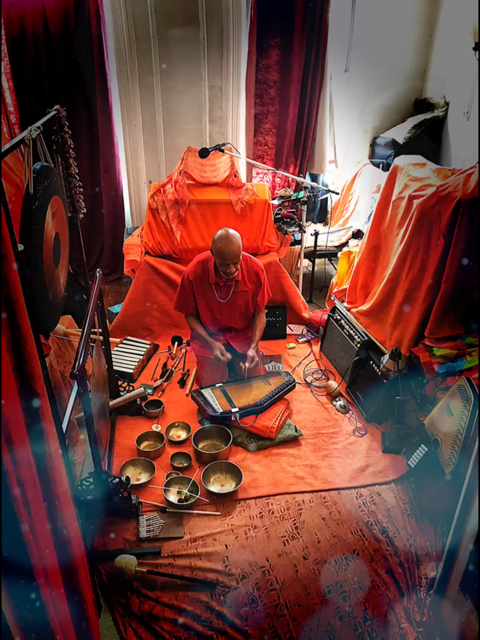 Laraaji channeling deep listening sound baptisms in Harlem. He is sitting in a room with a floor rug and cloth coverings in his signature orange, in front of him is his zither, sound bowls, and many other instruments.