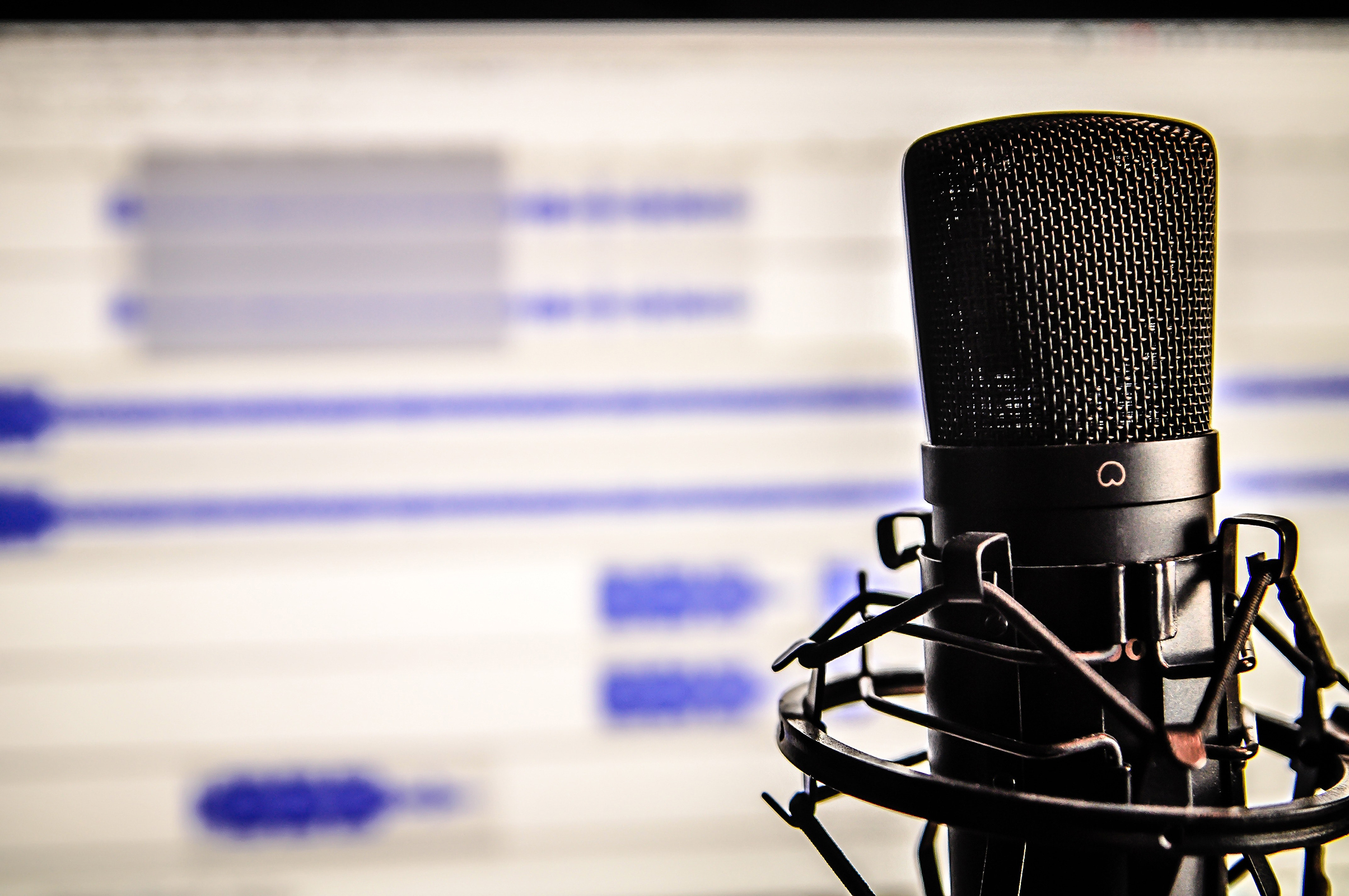 Microphone in front of audio editing software on a screen