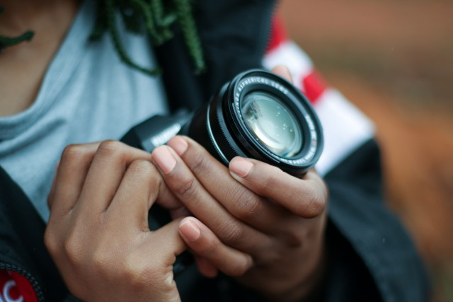A photographer's hands holding the lens and body of a camera.