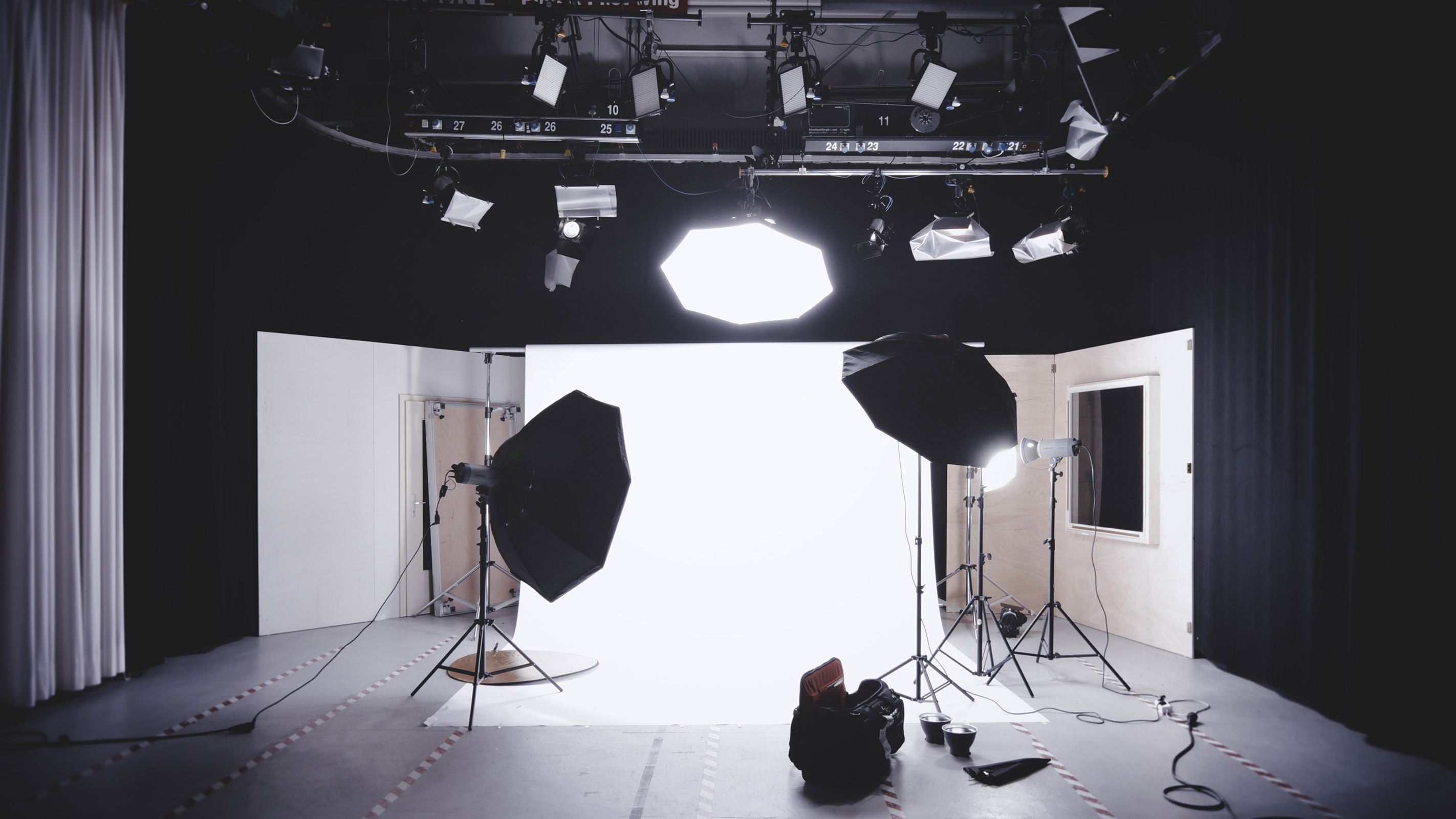 Bright softbox lights aimed at a white backdrop