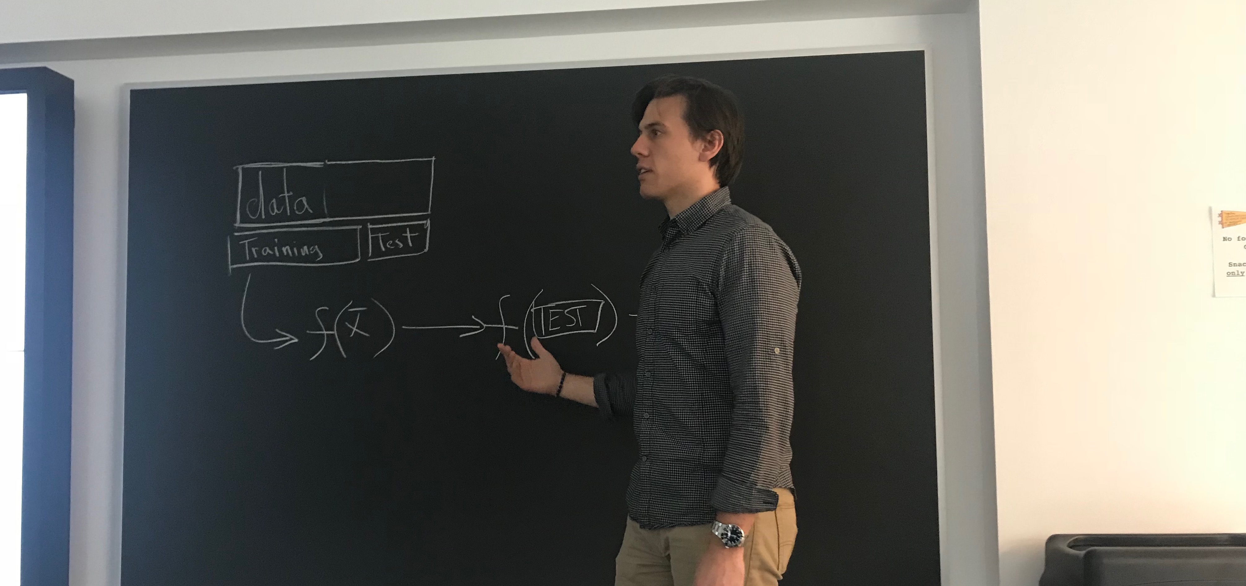 person teaching in front of blackboard, with a data-related diagram on it