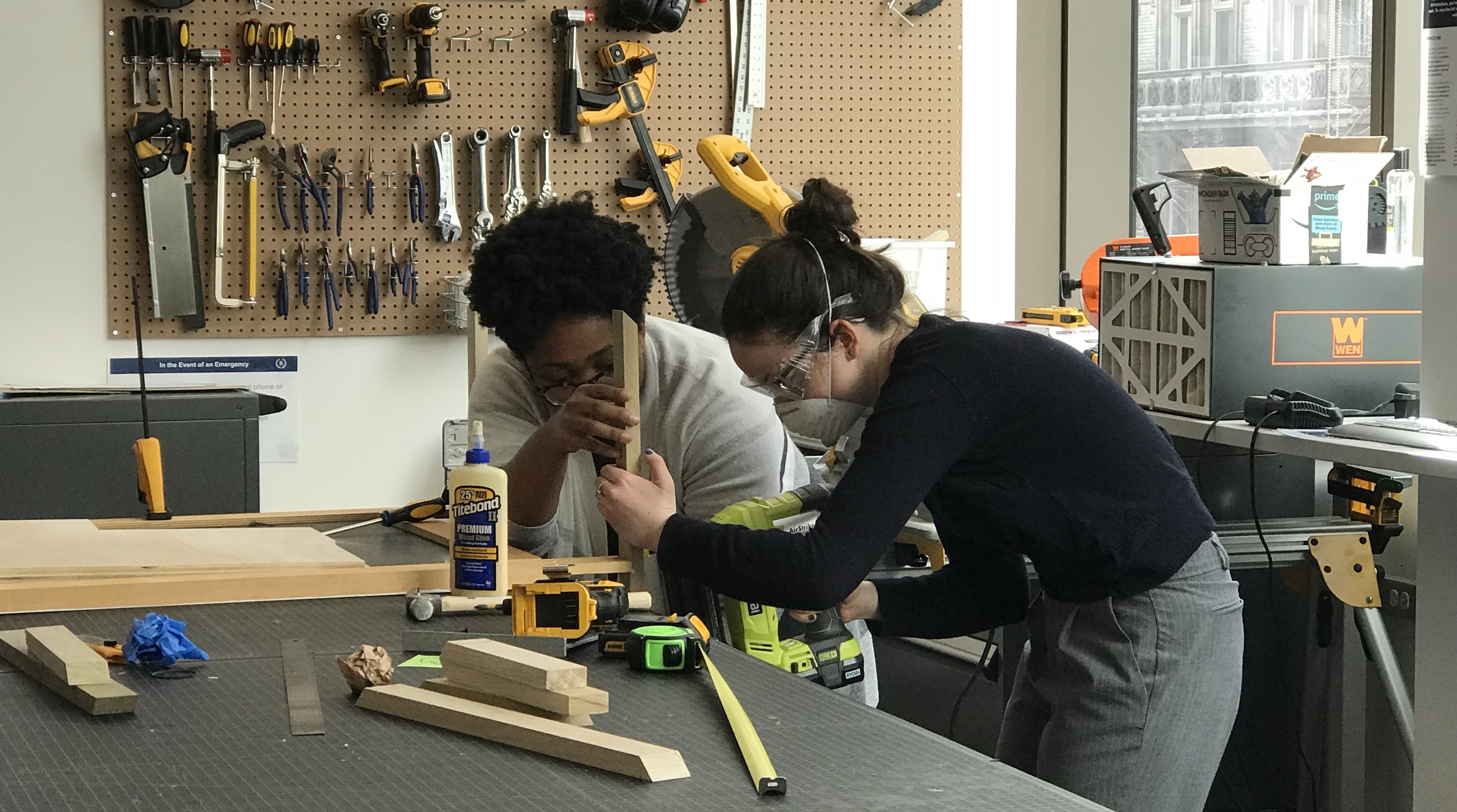 two people wearing safety goggles and using woodworking tools