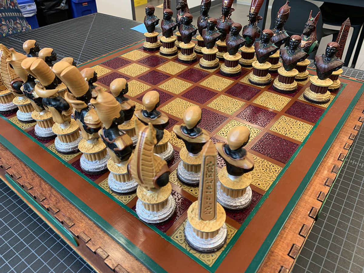 A chess set with pale yellow and burgundy squares on the board. The chess pieces are shaped like historical Egyptian figures.