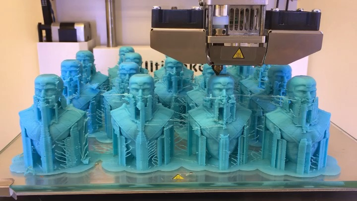 The chess pieces inside the 3-D printer. All the figures are cyan prior to being painted, because that's the color of the monofilament in the Design Center's 3D printing.