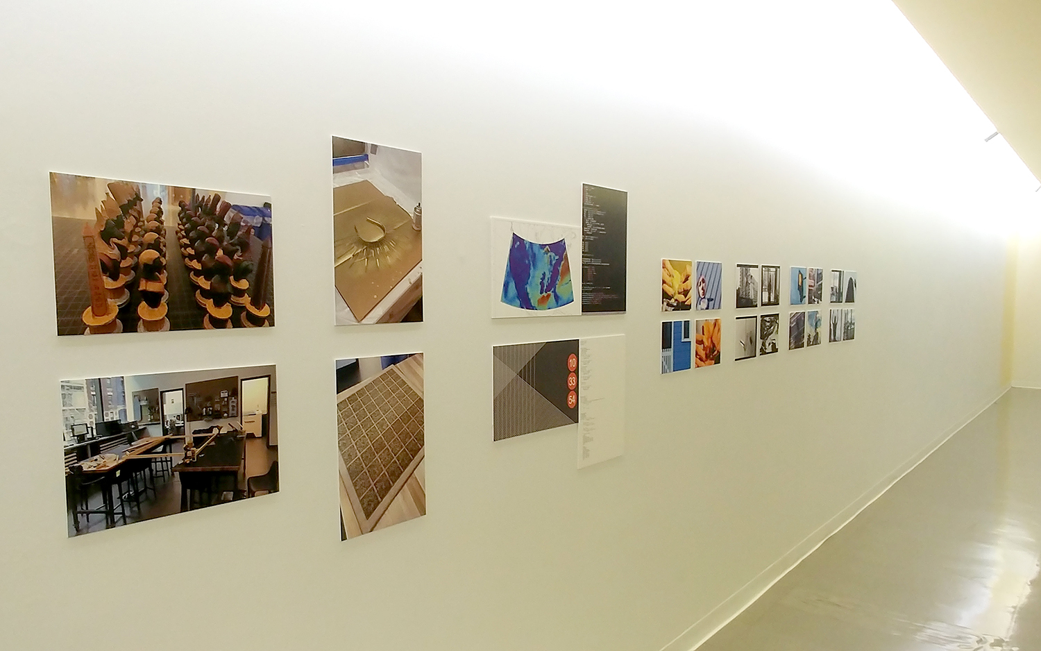 Photos of projects from the centers, hung on a long white wall.