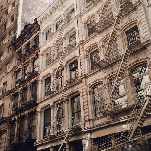 Facade of NYC tenement buildings, in muted colors