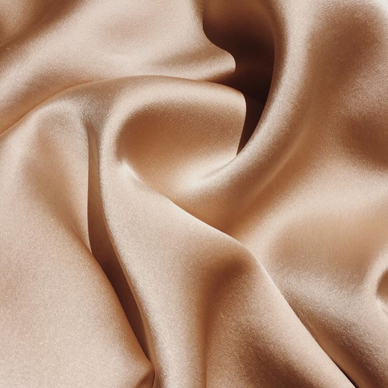 Shiny, smooth taupe colored fabric slightly wrinkled