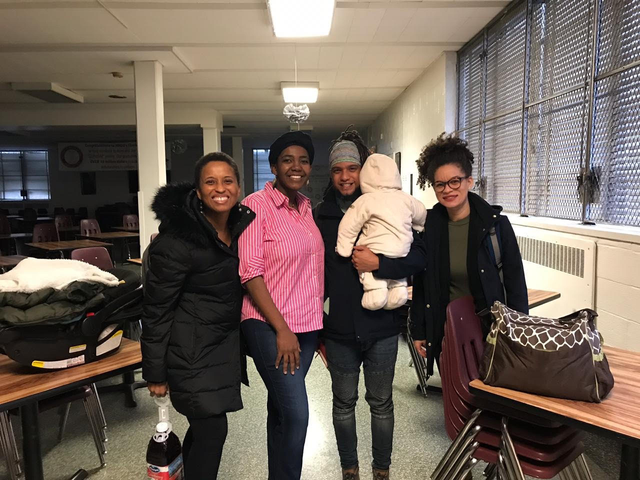 Miriam Neptune, Altagracia Jean Joseph, Alexis Francisco, and another facilitator stand in a row posing for the photo. Miriam is also holding a baby.