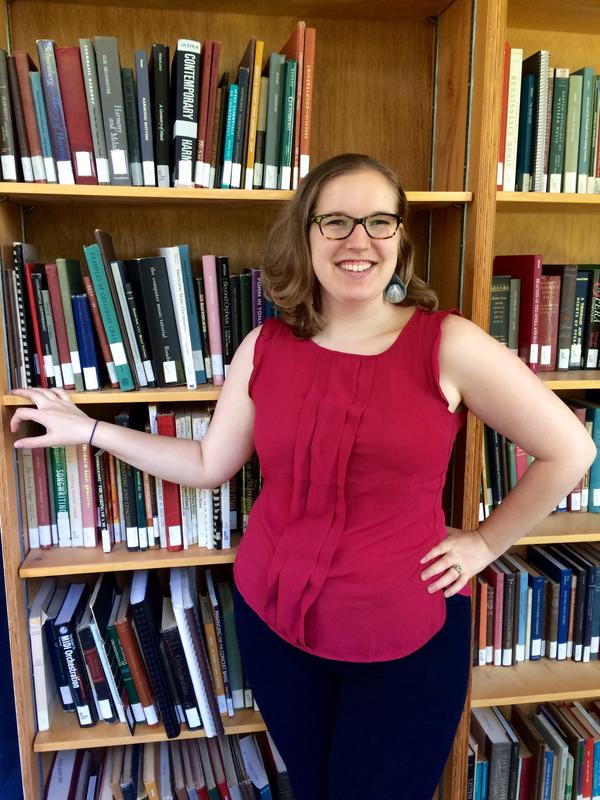Photo of librarian Charlotte Price standing in front of a bookcase