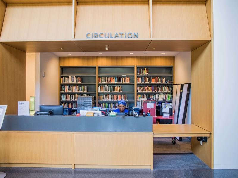 Big view of the circulation desk, with a student worker