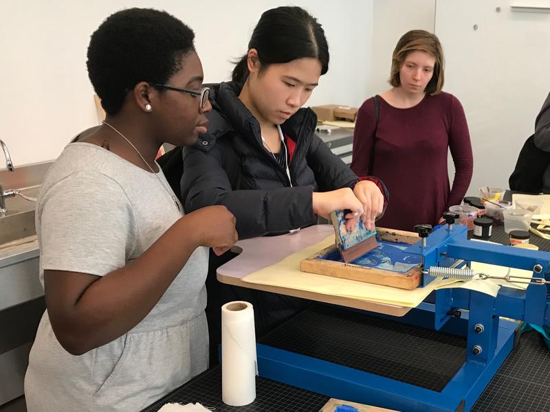 Students creating a print in the Design Center