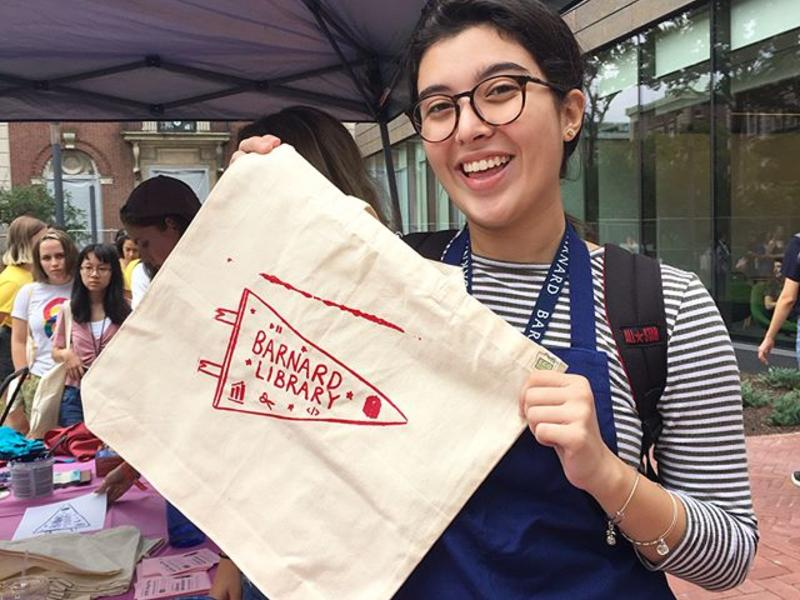 Screenprinting event. A student excitedly holds up a canvas bag with the Barnard Library pennant on it.