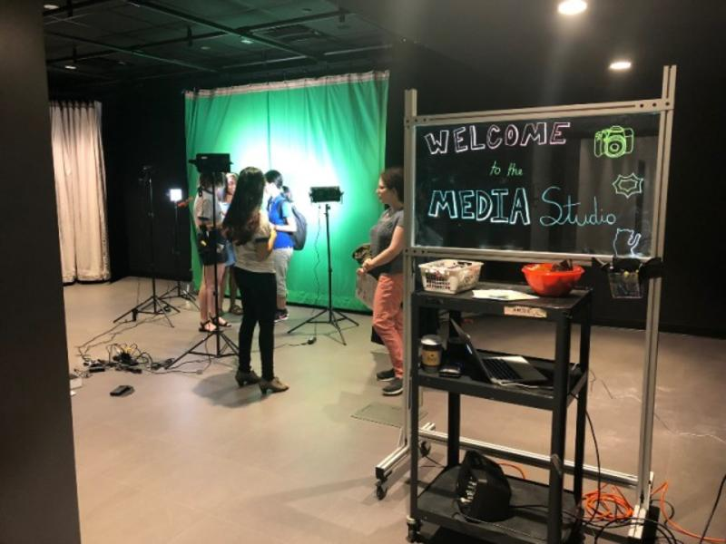 Media studio. Students stand near a green screen and cameras.